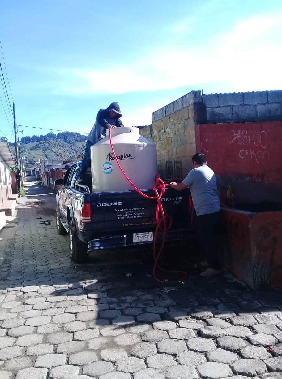 Collecting water to bring back to the project since the pipe burst in our section of town.